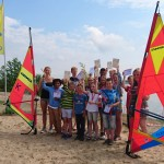 Die Windsurflehrer (v.l.n.r.) Ann-Sophie Meinecke, Frederik Sanders und Lea Beisheim freuen sich mit den erfolgreichen Nachwuchssurfern.